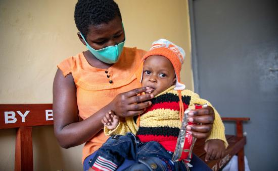 Jane Wanjiru give her baby son Mark Moses (11 months old) therapeutic food she received as part of his nutritional treatment at Mukuru Health Centre, Kenya.
